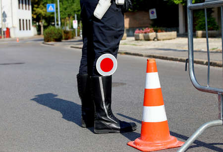 traffic warden: policeman with black boots and paddle traffic on the street in checkpoint Stock Photo