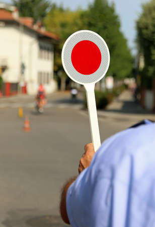 traffic warden: red paddle traffic in the street of the city