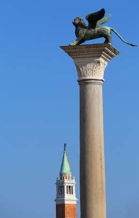 leon alado: estatua de bronce del león alado símbolo de la ciudad de Venecia en Italia a través de una columna con el campanario de la Iglesia de Saint Georges en el fondo