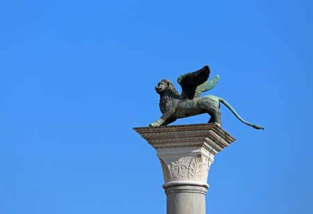 Bronze statue of the winged lion symbol of the City of Venice in Italy over a column and blue sky in background Stock Photo