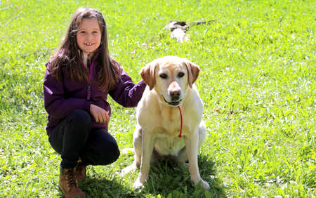 pretty smiling little girl with labrador retriever dog on the grass Stock Photo