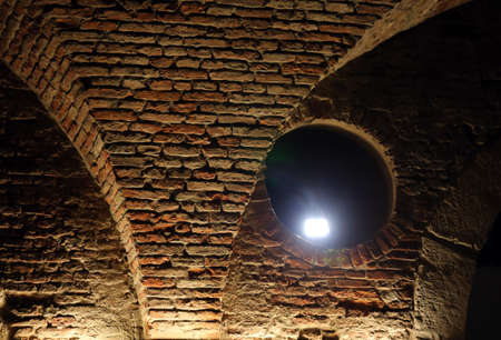 a nocturne: details of arches with bricks of the historic building at night Stock Photo
