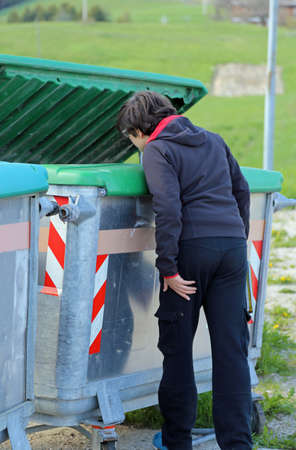 poor young boy looks into the garbage can in search of something Stock Photo