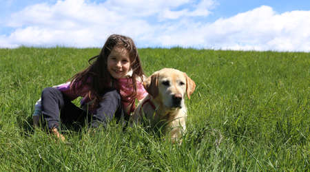 caucasian young girl and dog lying on green meadow in the mountains on a fine day