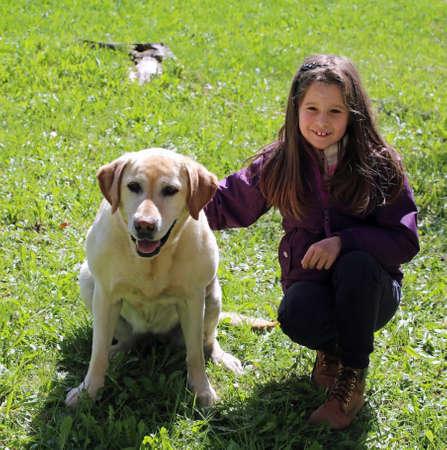 cute little girl with labrador retriever dog on the grass Stock Photo