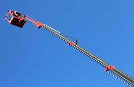 metal basket of an aerial platform with mechanical arm extended to maximum and blue sky in background