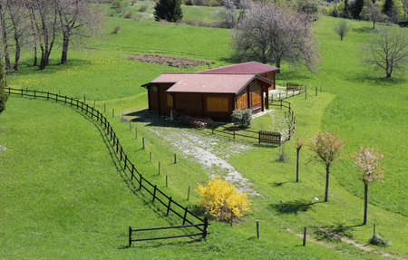 wooden chalet in the middle of the green lawn with wooden fence