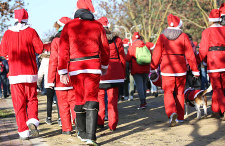 people with red Santa Claus clothes run during the sporting event called Running with Santa Claus in the public park of the city Stock Photo