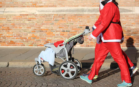 prams: Family with Santa Claus clothes walks with the stroller at Christmas Stock Photo