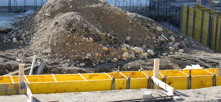 pile of earth and delimitation of outer walls of a house in construction site during the construction of the foundations of the house with reinforced concre