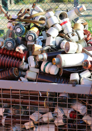 landfill: full basket in a landfill with pollution ceramic material and many old electrical insulators