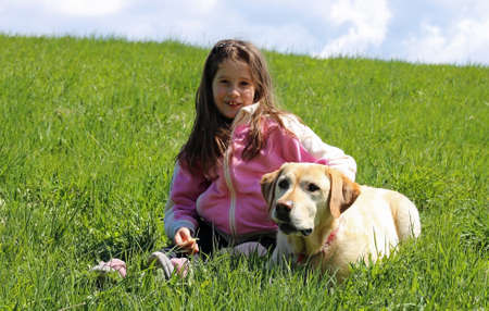 beautiful smiling little girl with labrador dog on the grass Stock Photo