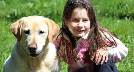 asperger syndrome: smiling young girl playing with labrador retriever dog Stock Photo