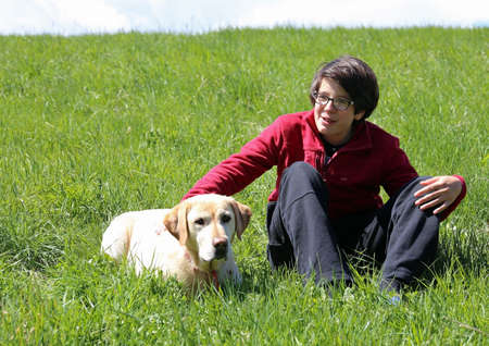 boy on the meadow in the mountains with his yellow Labrador Retriever dog