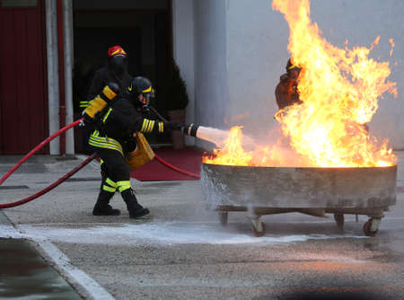 extinguishing: group of firefighters with oxygen tank extinguishing a fire with foam Stock Photo