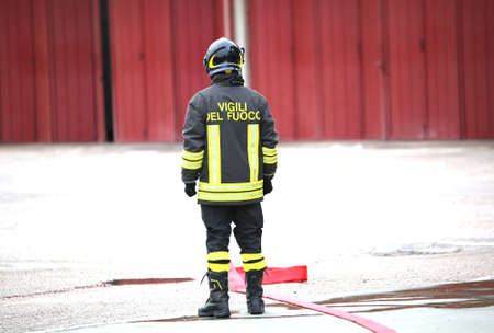 disconsolate: lonely Italian firefighters with the red fire hose  with the words in the protective clothes that means FIREMEN in Italian language Stock Photo