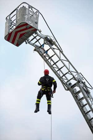 casco rojo: fireman with red helmet falls from the ladder truck basket