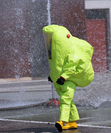 firefighter with big yellow suit against biological risk during a training exercise Stock Photo