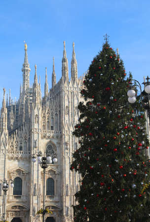 christmas ornamentation: huge Christmas tree with red silver and balls in front of the spectacular and immense cathedral of milan in italy Stock Photo