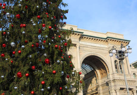 christmastide: Huge ornated Christmas tree and building dedicated to the King of Italy Victor Emmanuel II in Milan City in Italy