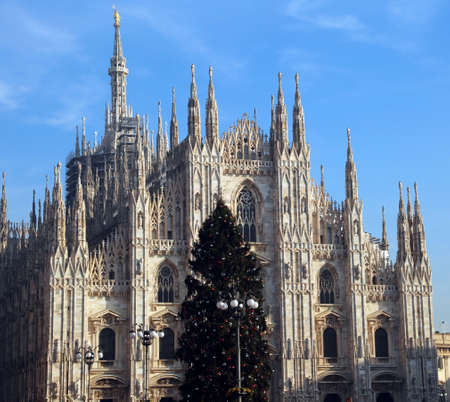 christmastime: Christmas tree with red silver and balls in front of the spectacular and immense cathedral of milan in italy