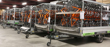 Vicenza, VI, Italy - January 1st, 2017: huge warehouse with the tow trucks full of bikes of the company Girolibero the principal european tour operator specialising in cycling holidays Editorial