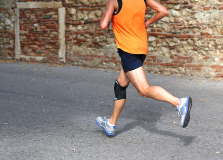 fast runner running fast with a knee brace to support muscle ligaments