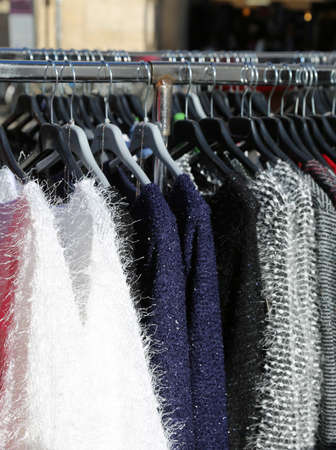 rummage: many winter clothes on hangers for sale