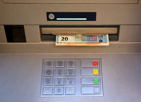 bankomat: electronic keyboard of an ATM with euro money coming out