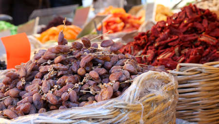 deglet: baskets of dates and dried tomatoes for sale at the fruit market of southern Italy