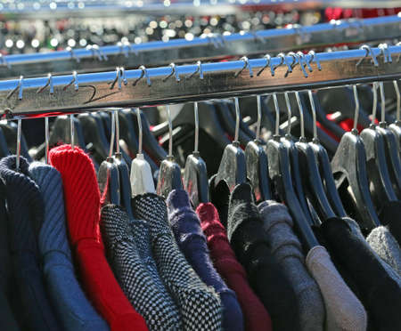 rummage: many winter hanging clothes for sale in the outdoor market