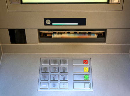 bankomat: electronic keyboard of an ATM with money coming out