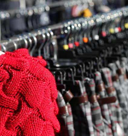 Red sweater wool and many winter clothes on hangers for sale in the outdoor market