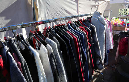 many winter clothes on hangers for sale in the outdoor market