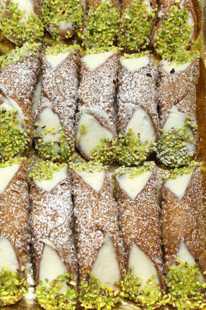 cannoli pastry: Background of delicious Sicilian cannoli with grated pistachios and cream