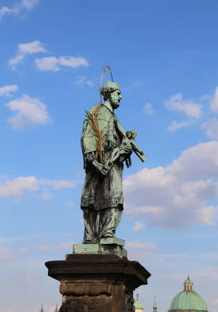 statue of John of Nepomuk at Charles Bridge in Prague at the site where the saint was thrown into Vltava River