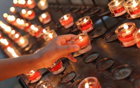 hand of young girl  turns on a red candle in church and then she says a prayer Stock Photo