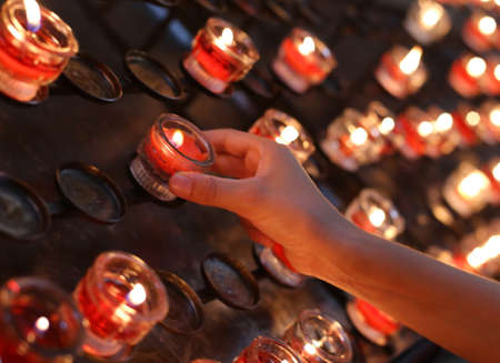 plea: child turns on a red candle in church and then she says a prayer for the family Stock Photo