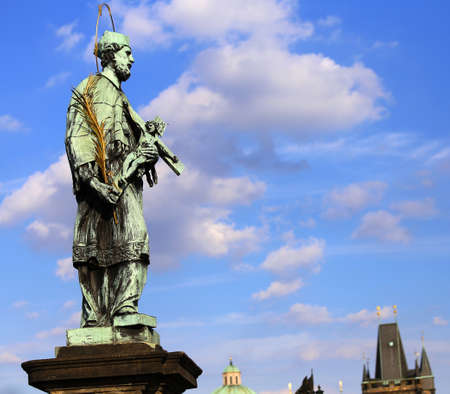 Bronze statue of John Nepomucene with halo and crucifix in Prague is protector from floods and drowning