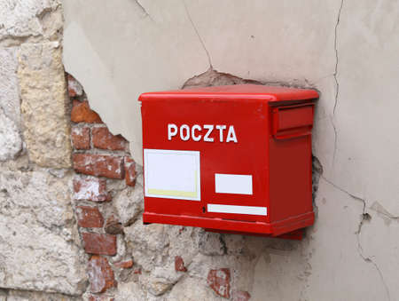 consignment: old red mailbox with the words POLISH POSTAL service Stock Photo