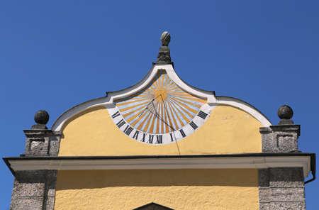 numeros romanos: antiguo reloj de sol con un palo en la pared del palacio viejo marca la hora uno y cuarto