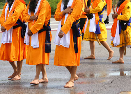 men of Sikh Religion with long orange clothes walk barefoot with swords in hand on the paved road