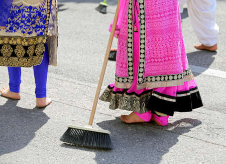 kameez: barefoot women of Sikh religion with colorful clothes sweep the asphalt road during the event