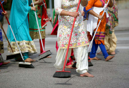 kameez: many barefoot women sweep the road during the ceremony along the streets of the city Stock Photo