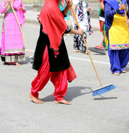 barefoot women of Sikh religion with clothes of many colors sweep the road during the celebration event in the city
