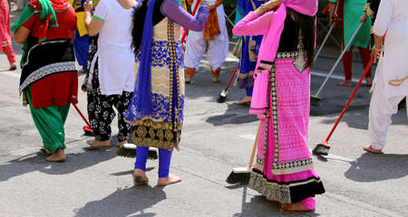 barefoot women with colorful clothes sweep the asphalt road during the event in the city Stock Photo