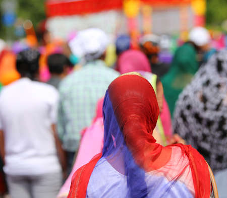 kurta: woman with a headscarf to cover her head during a gathering of people Stock Photo
