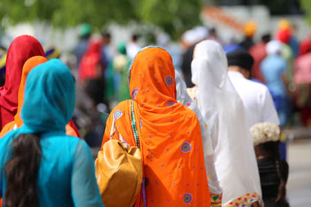 woman with orange headscarf and many people during a gathering of people in the city