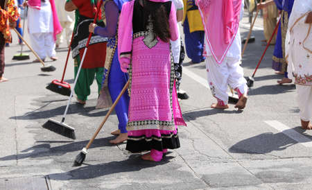 kameez: women with colorful clothes sweep the asphalt road