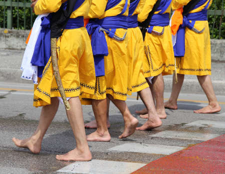 Five men of Sikh Religion with long dresses walking barefoot through the streets of the city during the religious event